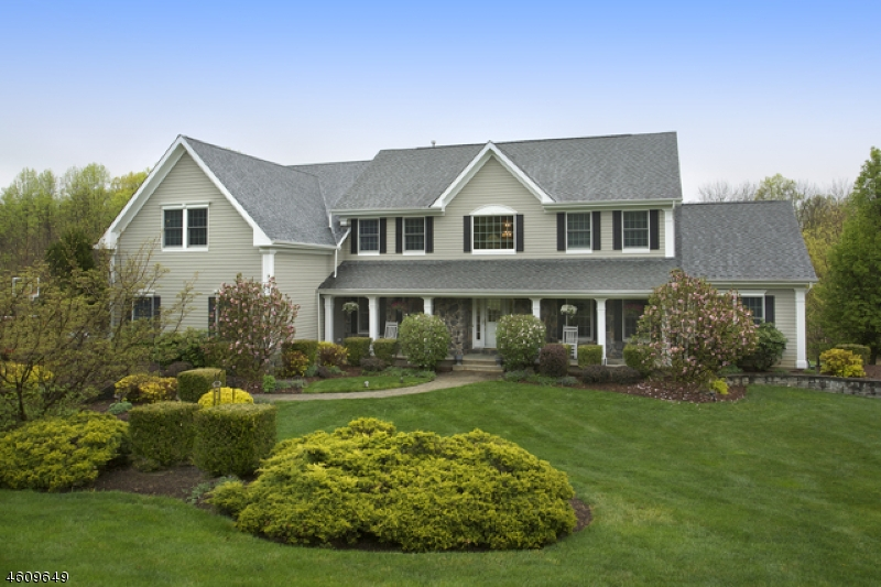 Privately situated at the end of a cul de sac on three lushly-landscaped acres, a Tewksbury Township Colonial enjoys a prime location. Views of the manicured acreage are enjoyed from every room. An ex pansive 3,968 square-foot layout offers additional space in the finished walkout lower level and bonus exercise room set over the three-car attached, oversized garage. Built in 2002 the floor plan contains four bedrooms and three-and-one-half baths. Stunning design elements include oak and Brazilian cherry hardwood floors, crown and applied moldings, a wood-burning fireplace and high ceilings. The setting features a tiered Trex rear deck overlooking a Carlton free form salt water pool with waterfall edged by a pebble-finished patio and a poolside wood and stone pavilion.