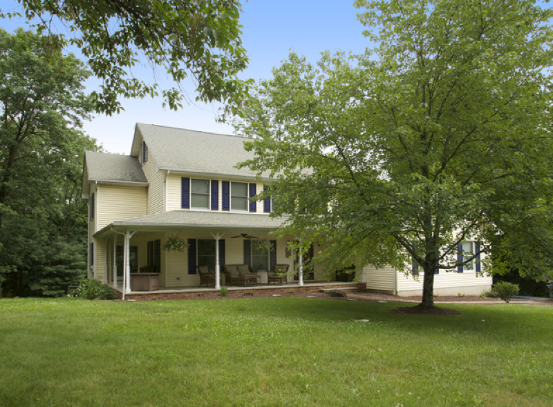 Country Colonial with welcoming wrap-around porch and finished walk-out lower level nestled on almost one landscaped acre.