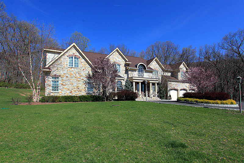 A majestic real stone front Colonial Custom-Built residence presides over three landscaped acres in Tewksbury Township. The open and wooded property borders protected conservation land and is sited on a peaceful cul-de-sac street overlooking mountain views. Outstanding details characterize the expansive 6,200 square-foot floor plan of four bedrooms, five full baths, a powder room and an attached three-car garage.      Built in 2008, this better-than-new Colonial is fitted with many custom updates and design upgrades. Highlights of the thirteen room floor plan are extra-wide red oak hardwood flooring throughout the home, four fireplaces, extensive molding treatments, transom-topped windows, French doors, a wet bar, high ceilings, built-ins and three levels of impeccably-finished living space.      Close attention to every detail becomes apparent in this home's sophisticated point of entry.  A set of mahogany front doors opens into an elegant entrance foyer fitted with a curved staircase edged by custom wrought iron railings, marble flooring, extensive trim and wall sconces.  The elegant living room features red oak hardwood flooring, wainscoting and a gas-log fireplace.  Lustrous red oak hardwood flooring continues into the formal dining room with extensive millwork including wide crown molding and wainscoting and majestic mountain views. Nearby, a well appointed butler's pantry with sink and wine refrigerator facilitates family gatherings.      Continuing the open flow of this Colonial is a two-story family room where the free-standing floor-to-ceiling gas-log, stone fireplace is a commanding focal point.  A wall of windows in the family room frames and welcomes in vistas of the landscaped grounds and beyond.  This dramatic room opens to the well-appointed gourmet kitchen. Customized with a host of commercial-grade appliances, the chef's kitchen offers Viking appliances including multiple wall ovens and a six-burner cook-top with exterior venting.  Black granite countertops, custom white cabinets, a center island with prep sink, decorative tumbled marble backsplash, storage pantry and a spacious, adjacent breakfast nook with access to the patios are other kitchen amenities. The main level also offers a flexible use opportunity for a first floor guest suite with private stone patio and an elaborate, adjoining tumbled marble full bath or an office/library or billiards room.  Completing the first level is the formal powder room, side porch and access to the garage and finished lower level.      Upstairs, the remarkable master suite begins in a spacious bedroom with walk-in closet.  The bedroom is joined by a charming sitting room, and both rooms enjoy the warmth of a gas-log fireplace. Luxurious amenities in the master bath are a jetted tub overlooking distant mountain views, an oversized customized frameless glass door shower with multiple body sprays and cherry wood vanities capped in limestone.  The second story offers two additional bedrooms, two luxurious full baths, plus a leisure room and secondary family room.      Additional gathering space is located in the full, approximately 2358 sq ft (2009) finished lower level, which provides beautifully detailed areas for exercise/gym, state of the art theater/ media and recreation rooms, wet bar as well as a full bath.      Home systems include multiple zones of efficient forced hot air propane heating and central air conditioning, central vacuum, private septic, well water and underground utilities.      Located in Hunterdon County's Tewksbury Township, residents appreciate a central location about an hour from New York City while still enjoying a tranquil setting in the heart of the Hunterdon Hills horse country.