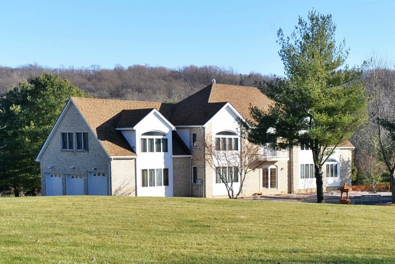 Magnificent LOCATION along Musconetcong RIver in very quiet neighborhood. House with 4 + acres has water view of Musconetcong River - far to the rear and below house. Formal LR & Dining room, Family room, Den, 3 BR, office, & Additional  IN LAW Suite (4th BR) with entrance from garage. Formal LR has Large windows and wood burning FP. Well cared for wood floors and ceramic tile. 3 Season room overlooks back yard, large pool, pool house and screen in gazebo. Lots of storage in additional garage. Outdoor security cameras.