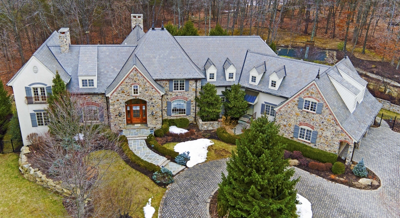 Majestic gated estate setting offers Stone and cedar Manor on tranquil cul de sac in Tewksbury set on 7.25 acres overlooking woodland views with easy access to Interstate 78. The sophisticated 8816 square foot residence with open floor plan of six bedrooms, five full baths and two powder rooms is professionally decorated and sublimely detailed. Outdoor amenities include paver circular drive, bluestone patio, 3 open porches, screened dining porch and built-in barbecue. The gracious interior contains maple inlay floors, marble and tile floors with medallions, rich millwork, five fireplaces and hand painted murals, Venetian plaster walls and glittering custom chandeliers of crystal, alabaster and bronze finishes. Introduced by a dramatic two-story foyer with curving staircase edged in gold leaf, main spaces include regal formal living and dining rooms, coffered ceiling cherry library, two-story great room with wet bar and chef's center island kitchen featuring upscale appliances and sun-splashed breakfast room.  The spacious bedrooms include a master suite with fireside sitting room, luxurious bath and first floor guest suite.  The fabulous1800 square foot finished walkout lower level presents cherry bar, fire-lit recreation room, home theater, billiards room and half bath. Other notable aspects are the built-in generator, elevator for all 3 levels, iPad compatible sound system and attached three-car garage. Slate roof.