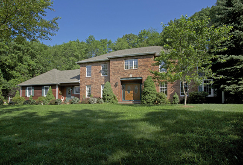 Stately Brick Front Colonial nestled on 3.58 landscaped acres at Bridge Hollow estates.
