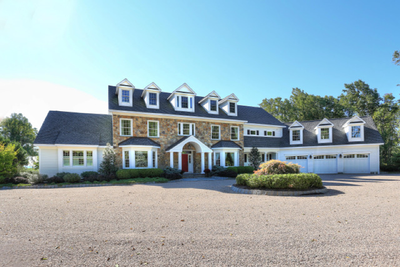 "The picturesque countryside of Tewksbury provides an enviable backdrop for a custom-built Bucks County-inspired country estate featuring a classic stone façade. The elaborate five bedroom, five full bath and two half bath floor plan presents over 7,100 square feet of opulent living space.  Set on 22.91 secluded, farmland assessed acres bordered by conservation land, views stretch out as far as 100 miles, taking in stunning panoramas of the rolling hillsides and bucolic scenery.       Approached by a long, winding circular drive, this majestic home takes full advantage of its spectacular views with heated covered front porches and heated patio.  Inside, notable details include rich ash moldings, coffered and exposed beam ceilings, bay window walls, three fireplaces and distinctive flooring of herringbone brick, slate, travertine, mahogany and ash.        The grand introduction to this classic fourteen-room estate home is a two-story foyer with faux painted walls and exquisite Travertine marble featuring marble inlays.  Leading from the foyer is a formal dining room fitted with knotty wood flooring and a sunny bay window.  An adjacent butler's pantry offers cherry cabinets capped by stone counter-tops, two refrigerator drawers and a bar sink with oil-rubbed bronze fixtures. A den or study presents a bay window, wide board mahogany floors and recessed lighting.  Chef's will feel right at home in the expansive gourmet kitchen designed by Morgan House Design Center of Clinton.  Striking design elements include walnut Plain & Fancy™ cabinets in a rich cherry stain, Cordova granite counters, a backsplash fashioned of glass, marble and stone, floor-to-ceiling stone walls, slate tile floors and a spacious center island illuminated by pendant lights.  This oversized island offers a sink and breakfast bar seating.  Upper-end appliances consist of two sets of Fisher-Paykel™ dishwashers; a 60-inch Wolf™ six-burner propane gas stove with griddle; stainless steel Wolf™ exhaust with pot filler; stainless steel Sub-Zero™ refrigerator; stainless steel microwave and stainless steel Dacor™ expresso maker.  Sliding glass doors in the breakfast area reveal a 1,000 square-foot Ipé™ Brazillian mahogany deck for outdoor dining and entertaining. Grandly-scaled for large gatherings, the two-story great room is enclosed by three window walls and presents diagonally-placed ash flooring featuring coffee-stained inlays, exposed beam ceilings, a balcony overlook, chandelier and glass door to the deck. Centering this inviting room is a dramatic floor-to-ceiling stone fireplace which can be fueled by propane.  A built-in maple wet bar streamlines entertaining. Another option for friends and family on the first floor is a spacious sound-proof movie theater complete with professional-style seating tiers and projection screen. The main floor also provides two stylish powder rooms, a well-equipped laundry room, a rear staircase and an attached three-car garage with a pet bathing area and doorway to the deck.       Situated on the first floor for an exceptional measure of privacy, the elegant master suite offers wide plank birch floors, a propane gas stone wall fireplace set into a corner, high angle ceilings and an expansive (10'x20') walk-in closet fitted with wardrobe organizers. An atrium door opens to the heated bluestone deck with fantastic views. In the sophisticated master bath, sumptuous details inlcude travertine tile flooring and walls, a cherry dual sink vanity topped in granite, private water closet and ""bubbler"" air jet tub.  A state-of-the-art steam shower is oversized and offers nine shower heads, a marble seat, clear glass door and decorative mosaic and listello tilework.       A main staircase ascends to the second story balcony area overlooking the towering great room below.  This level contains a bedroom suite with sitting room and private bath, another bedroom connnected to a private bath, and two additional bedrooms sharing a full bath.  The oversized bonus room set above the garage is carpeted and has three roomy storage closets.       Of special note are the outdoor amenities of this estate-caliber home. The covered front porch presents a barrel ceiling and bluestone flooring, while the porch and rear patios each have a Warm-Zone™ outdoor heating system in place. The rear yard offers a charming arbor and a large fireplace fueled by gas or wood. There is a handy outdoor bath with slate floors, a slate shower and clear glass vessel sink set into a redwood pedestal.  Impressive architecture is graced by a façade combining stone and Hardiplank™ siding, which is capped by a Timberline shingle roof with a gable configuration.  All the windows in the home are Andersen™ thermopane in a variety of styles such as casement, double hung, sidelight, transom, custom shape and fixed.      Mechanical workings include multiple zones of propane gas heat with air filters and humidifiers on the furnace, central air conditioning, a whole-house backup generator, water filter and softening sytem, comprehensive home security system, integrated sound system, central vacuum, a tankless propane-fired hot water heater, radiant heated floors in select rooms, private septic, well water and underground utilities.      Tewksbury Township in Hunterdon County contains the historic villages of Mountainville and Oldwick.  These hamlets boast a charming mixture of Victorian, Federal, New England and Georgian style homes.  Interstate highways 78 and 287 are nearby, providing travel to cosmopolitan centers and corporate hubs.  The proximity of the interstates brings Newark International Airport within 40 minutes and downtown New York City is just 50 minutes away."