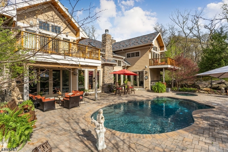 Fenced yard around heated gunite pool and spa. Enjoy dining on the patio surround or sitting under the covered porch. Two balcony decks off master & guest bedrooms.