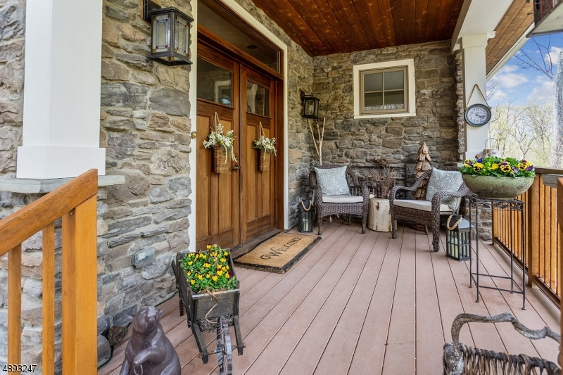 Stately approach with covered entry shows off the exterior details from gardens, stone work, wood work and nature.