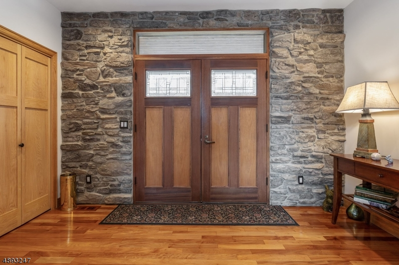 Foyer shows offer stone accent walls. Solid wood doors with mahogany inlay. Wide plank wood flooring