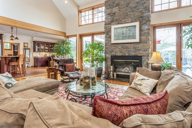 Field stone floor to ceiling fireplace. Custom built-in TV behind picture over mantel. Plank hardwood flooring. Sweeping open floor plan to outdoor lakefront, pool and open to dining & kitchen.