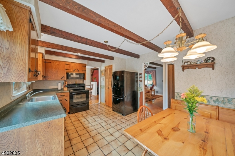Off the living room is the country kitchen with tile flooring and wooden beamed ceiling, sliders to the huge deck outside.