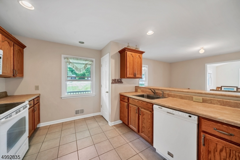 The guest/in-law suite has its own kitchen with tile flooring, breakfast bar and lots of storage.