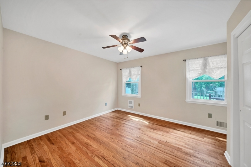 The guest/in-law suite has a bedroom with hardwood floors, lighted ceiling fan, double closet and access to the full bath.