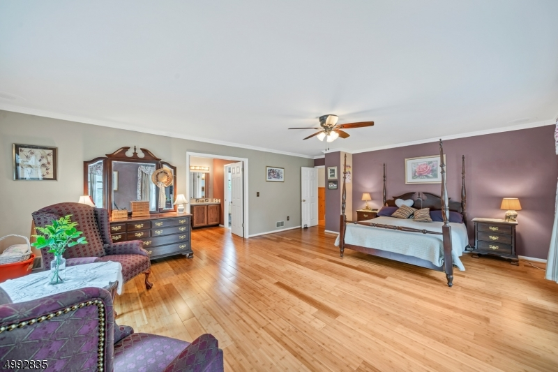 The primary bedroom has bamboo floors with a large picture window, crown molding and a lighted ceiling fan.