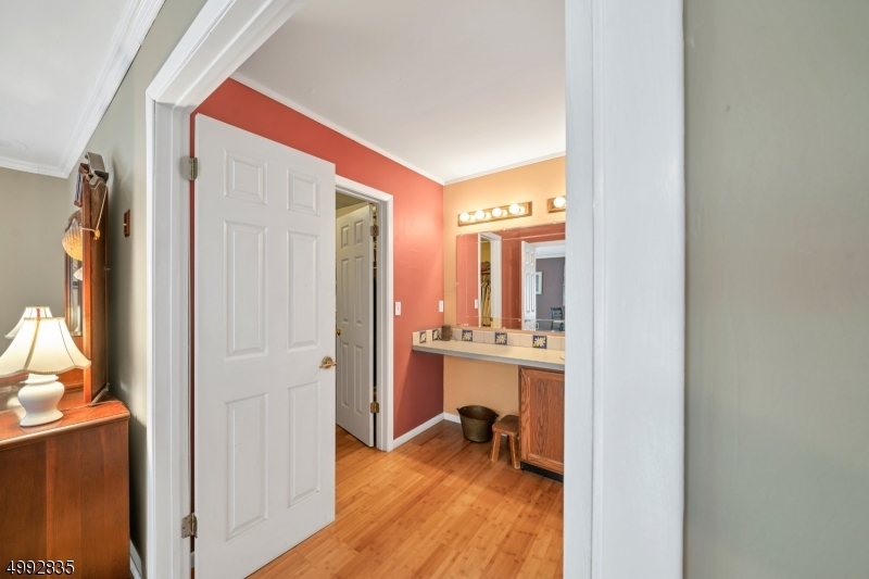 The dressing area has a walk-in closet, sink and vanity with a large mirror.