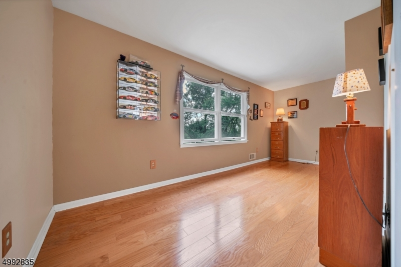 A second level office with hardwood floors has a large picture window that overlooks the lovely backyard.