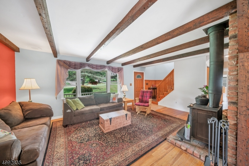 The living room has wooden beamed ceiling and hardwood floors.