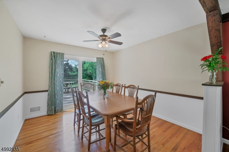 The dining room has hardwood floors, sliders to the huge deck outside, chair rail and a lighted ceiling fan.