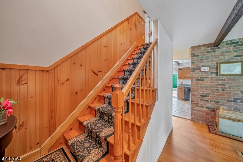 An extra-wide staircase leads to the second level with wainscoting.
