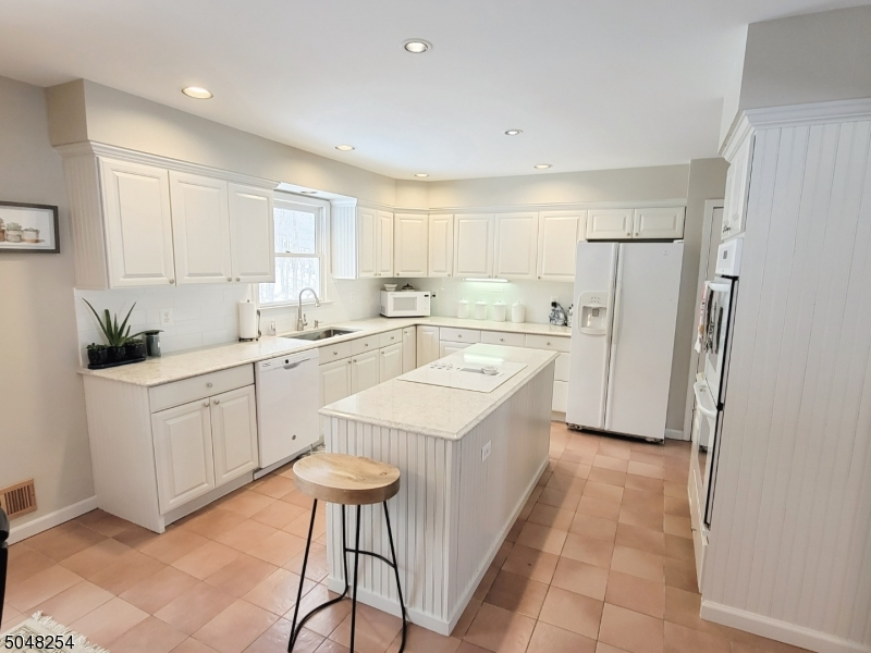 Charming white kitchen.  Newer counters, backslash, dishwasher and cooktop
