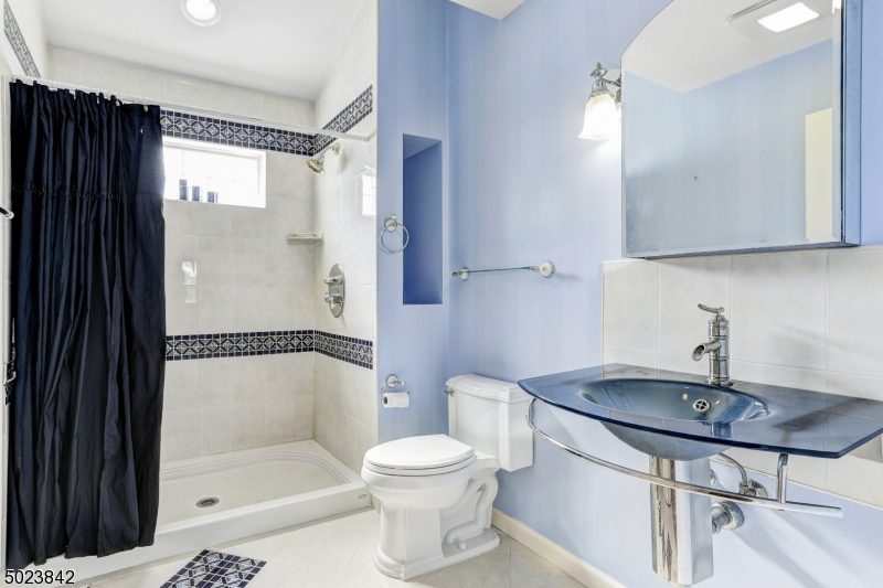 Over sized shower stall with decorative tile with vaulted ceiling.