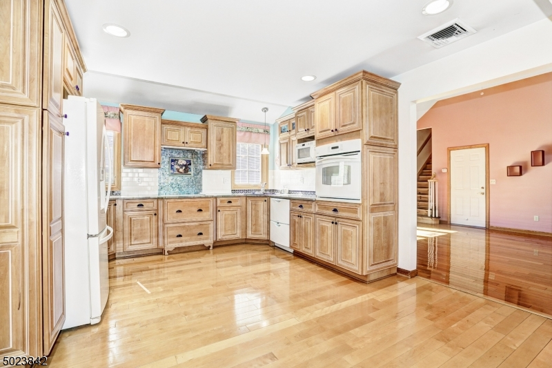 Beautiful kitchen with decorative tile, wood floors, recessed lighting, open to dining room and great room.