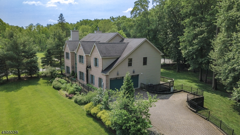 This gorgeous aerial view shows the gorgeous private property surrounding this stunning luxury estate! Beautiful brick paved driveway with an extra parking area to the right of the garage.