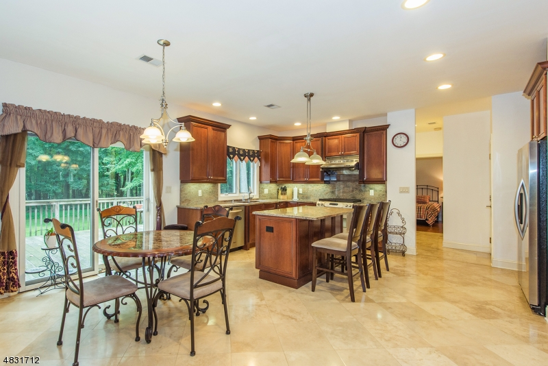 The stunning Eat-In-Kitchen features cherry cabinets, granite counters, center island w/breakfast bar, pantry, SS appliances, breakfast area, tumbled marble floors and sliders to the large deck.