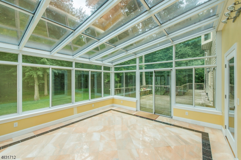 This stunning Sun Room features heated marble floors. Beautiful views of the park-like property! Great space for an office with a view, too!