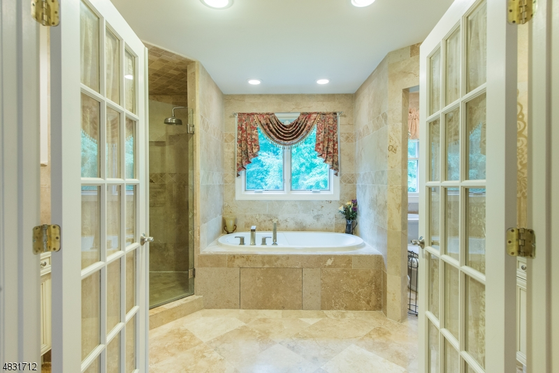 French doors open into a luxurious MBR Bath with two separate vanities, jetted tub and separate shower.
