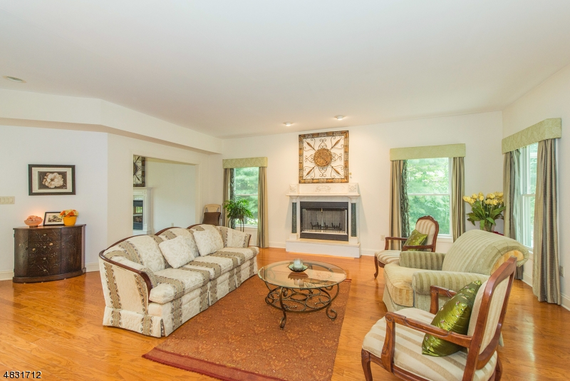 The stunning family room features a fireplace, gleaming hardwood floors, access to the sun room and opens to the kitchen and the living room!