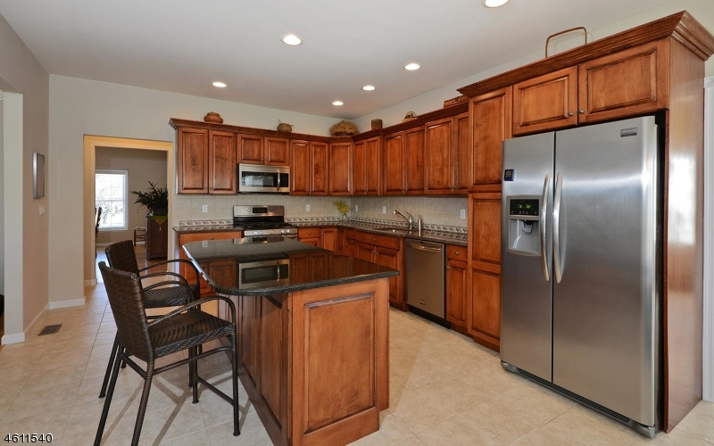 Custom kitchen with granite tops, stainless steel appliances and cabinets by Lutz.