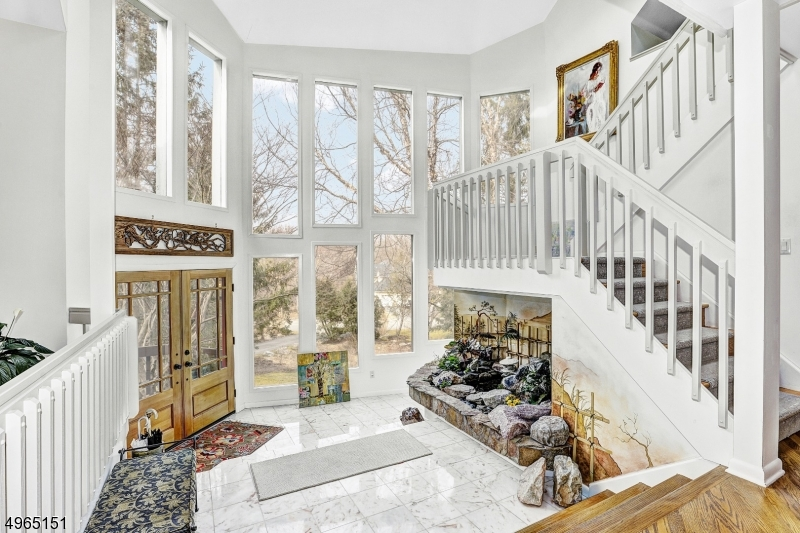 Grand, tranquil marble entry foyer with natural stone water feature. Two story wall of windows and natural sunlight.