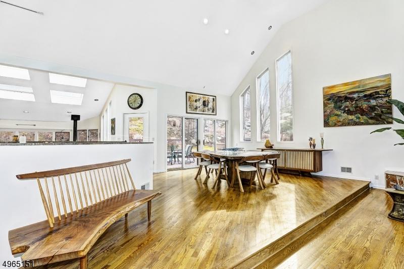 Set in open floor between living room and kitchen. Wood floors. Two sliders to deck overlooking beautiful naturescape.
