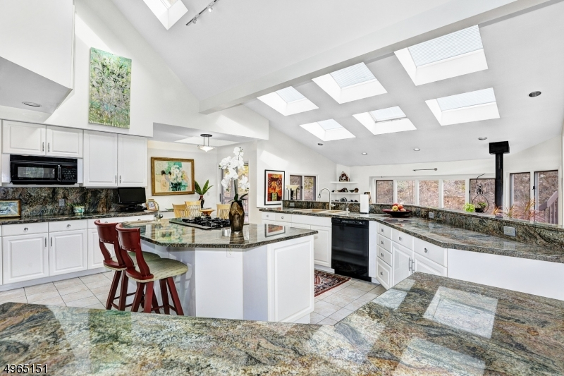 Magnificent eat-in kitchen. Center island with breakfast bar, gas cook-top and utility sink. Massive granite counters. Tons of natural sunlight from adjacent rooms and skylights.