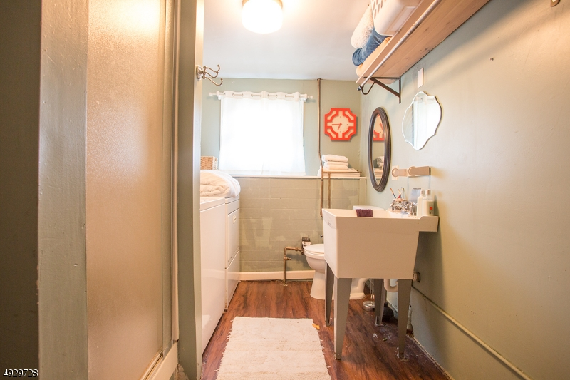 laundry room has toilet sink and stand up shower