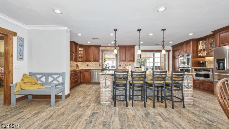 Gorgeous stone and brick 8 x 5 granite center island with breakfast bar. Recessed lighting. Door access to patio pavilion.