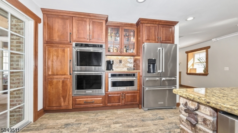 Kitchen-Aid appliances include refrigerator, dishwasher, double convection wall oven, microwave convection oven. Wine refrigerator.