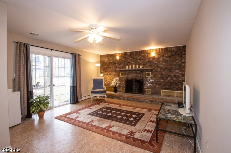 Family Room - Sconces on Brick Wall, Wood-Burning Fireplace, Sliders to Patio.