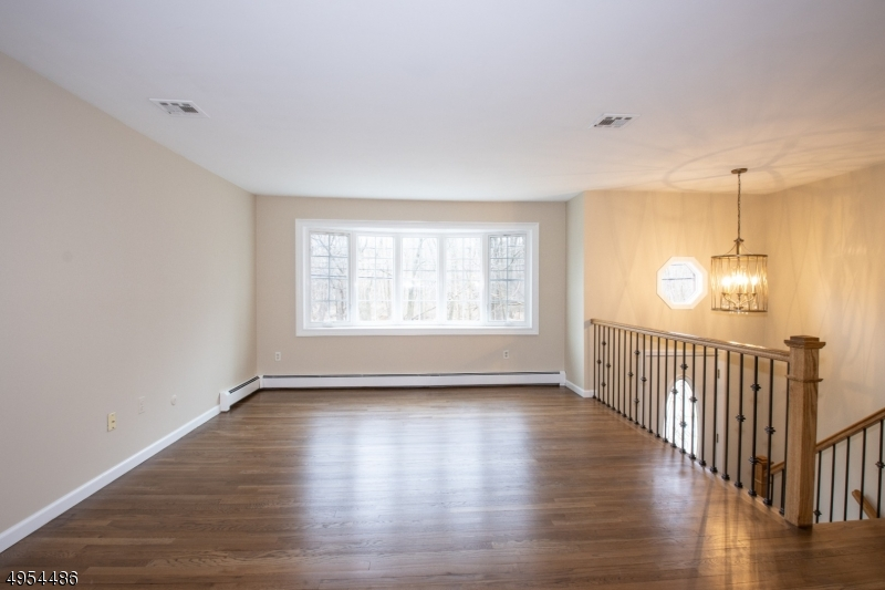 Light, Bright Living Room with Updated Railings, Thermal Casement Window and Newly Refinished Wood Flooring.