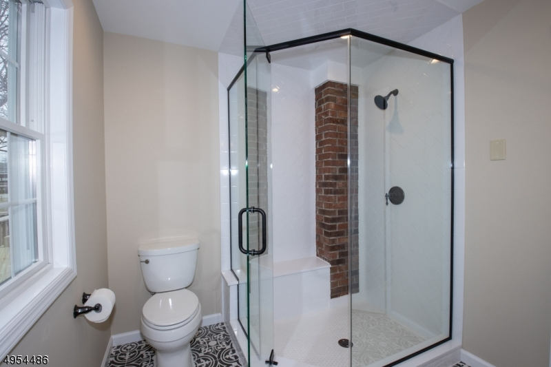 Oversized Herringbone and Brick Stall Shower with Clear Glass Doors.