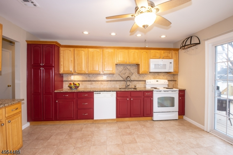 Kitchen with Granite Countertops, Lots of Cabinets and Pantry.  Sliders to Rear Deck.