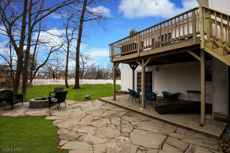Large Rear Deck Off of Kitchen with Concrete Patio Off of Family Room and Stone Patio with Fire Pit.