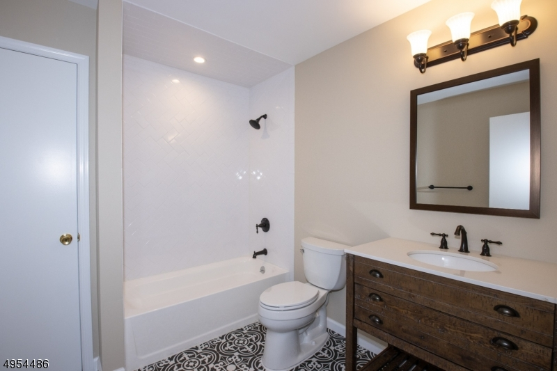 Brand New Generously Sized Main Bath With Tub-Shower, Herringbone Tile, Tile Floor and Linen Closet.