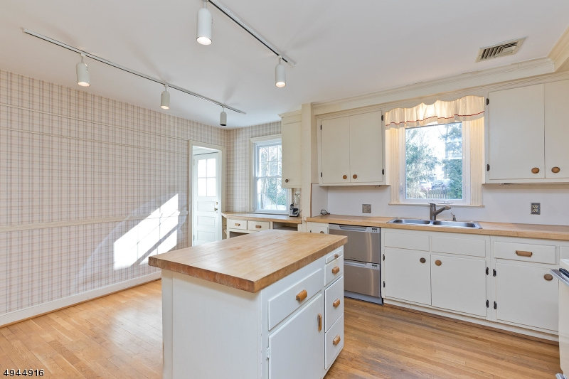 The Kitchen Island separates the workspace from the Dining Area. The Laundry room sits between the Kitchen and the interior Entryway to the Built-In Garage. There is also a door to the Deck and Garden.