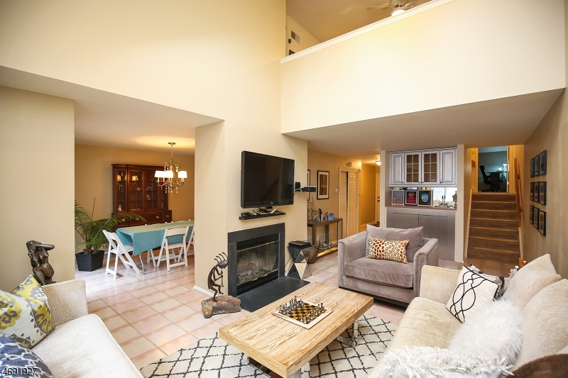 Look at this great room.  Double Height Ceilings, Skylights, Loft and wood burning fireplace.
