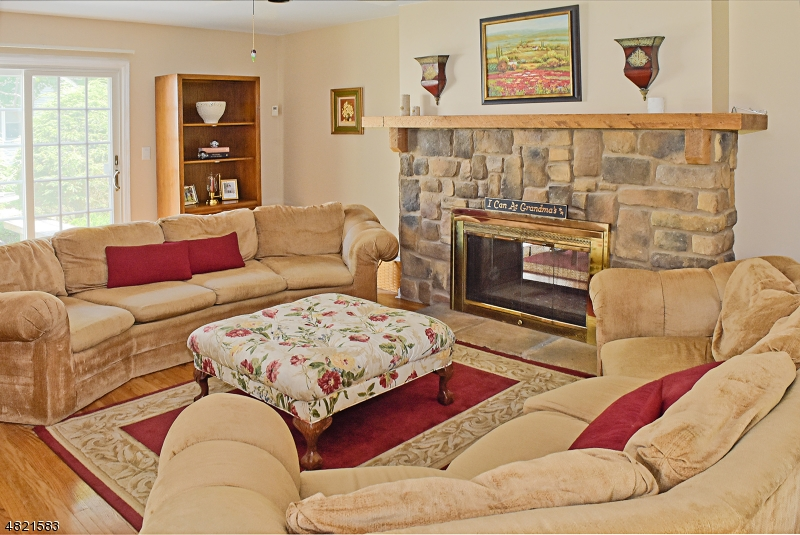 Gleaming wood floors, 2nd set of sliders to side deck, and  Rustic stone F/P add to allure of this inviting room