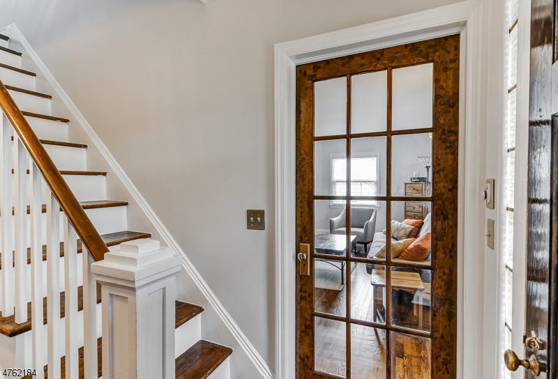 This natural wood french door offers a peak into the living room.