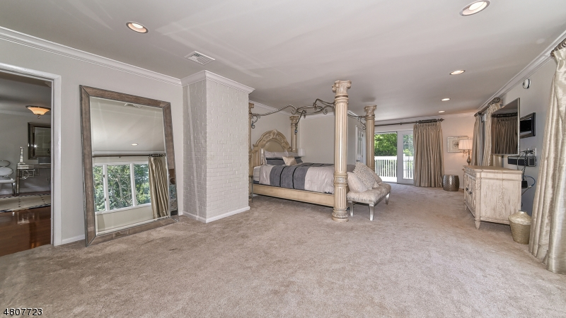 Spacious master suite with balcony overlooking expansive view of front property.