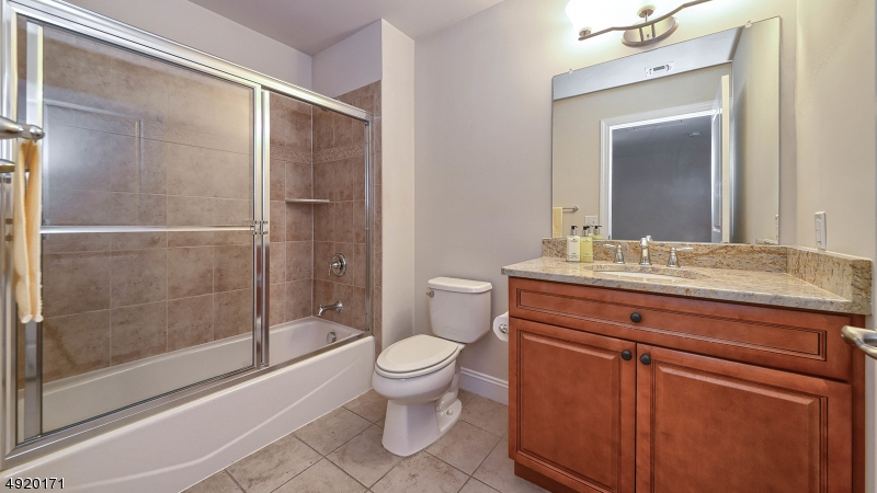 Tub/shower in main bath, also with granite counter top.