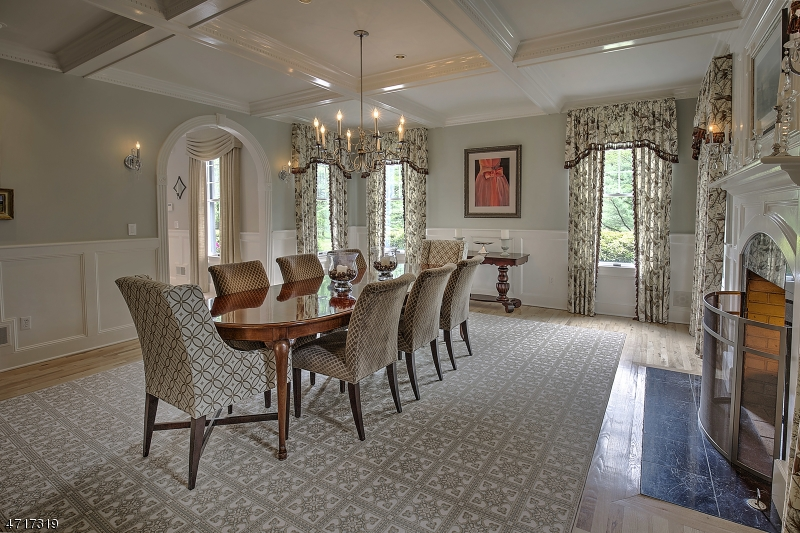 Gracious size dining room has coffered ceiling, paneling and moldings, and elegant fireplace.