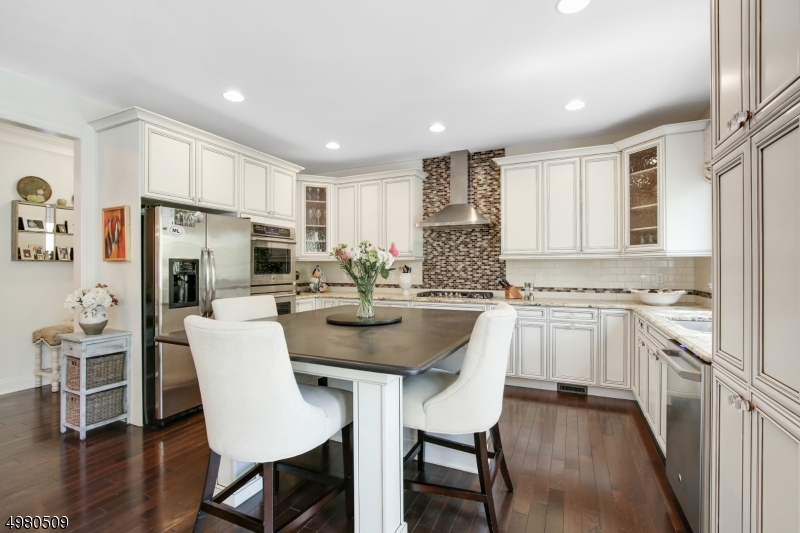 White cabinetry, granite countertops, island for eating