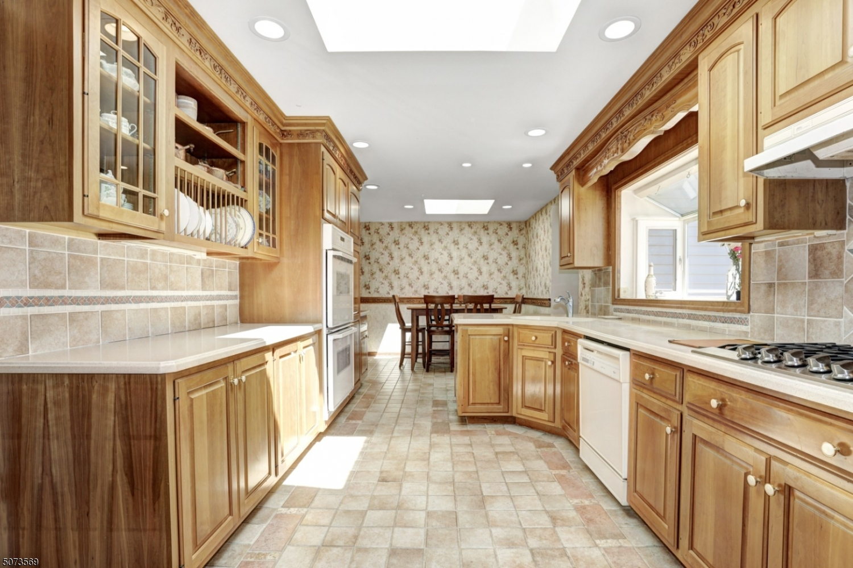 Custom kitchen with cherry cabinets, extensive moldings, recessed lighting, skylights, tile backsplash.